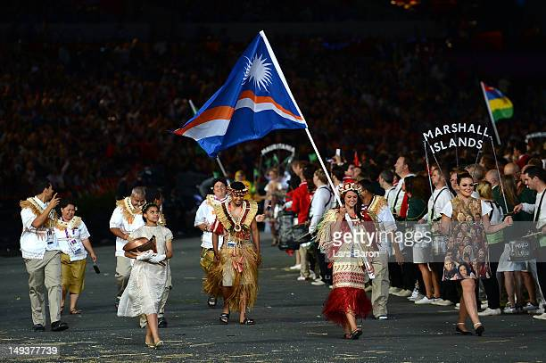 Haley Nemra of the Marshall Islands Olympic athletics team carries her country's flag during the Opening Ceremony of the London 2012 Olympic Games at...