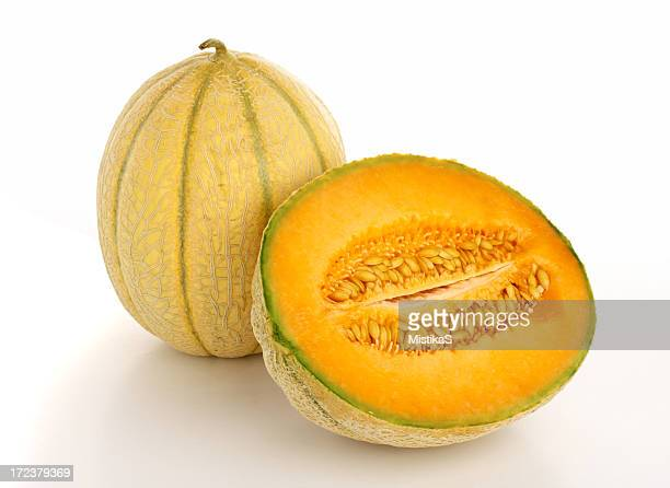 Half a cantaloupe next to a full cantaloupe