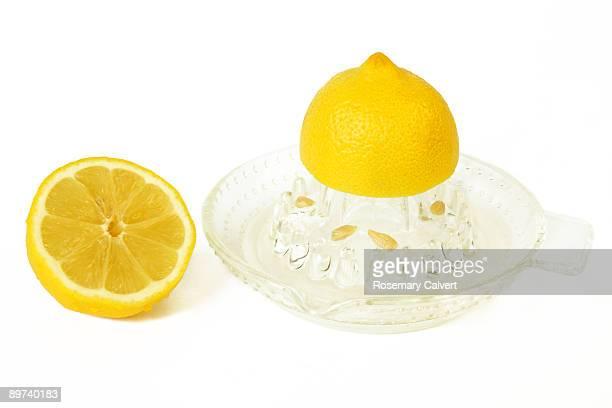 Half a lemon being juiced with half beside it.