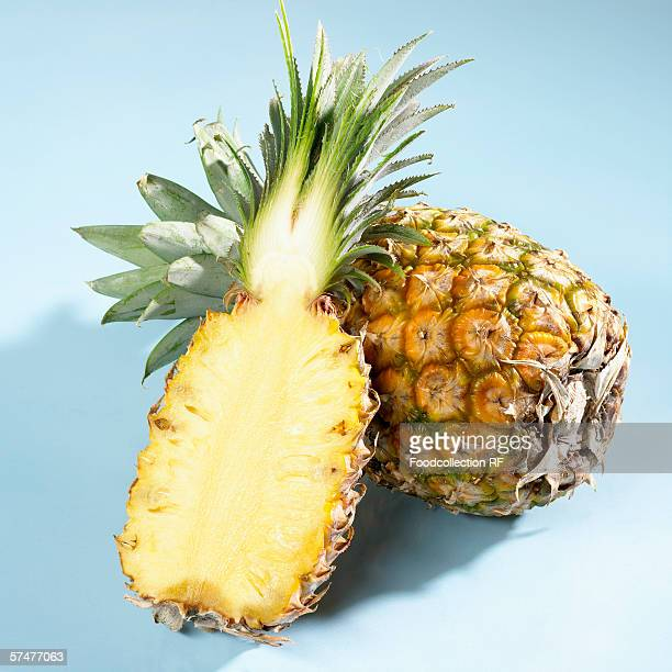 Half a pineapple in front of a whole pineapple