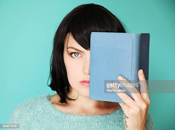 half a woman's face covered with a blue book - rekha garton stock pictures, royalty-free photos & images