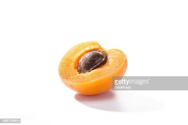 Half an apricot with the stone in against a white background