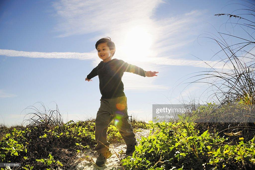 Half Asian Young Boy Running on a Beach Path : Bildbanksbilder