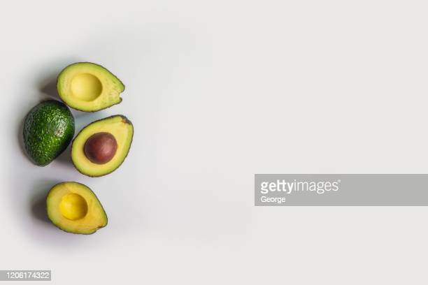 half avocado on gray background - avocado stock pictures, royalty-free photos & images