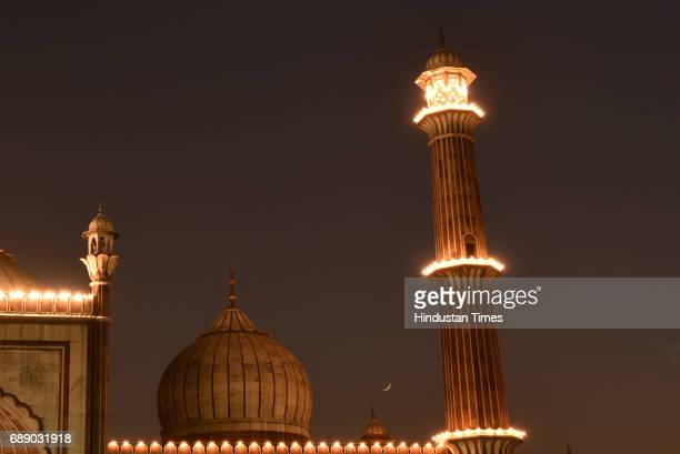 Half Crescent Moon is seen over illuminated Jama Masjid to mark the beginning of the holy fasting month of Ramadan on May 27 2017 in New Delhi India