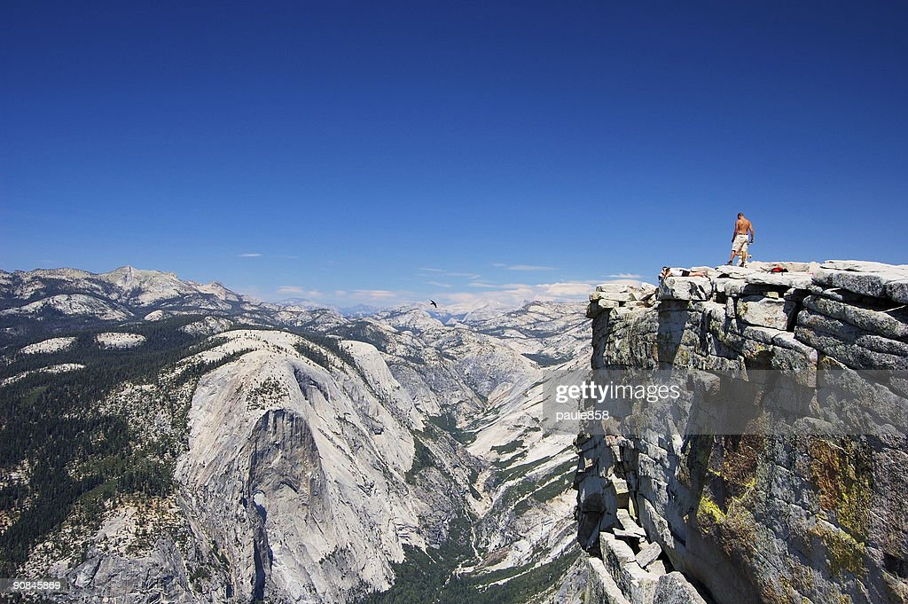 Half Dome rock with snow and person standing on the edge : Stock Photo