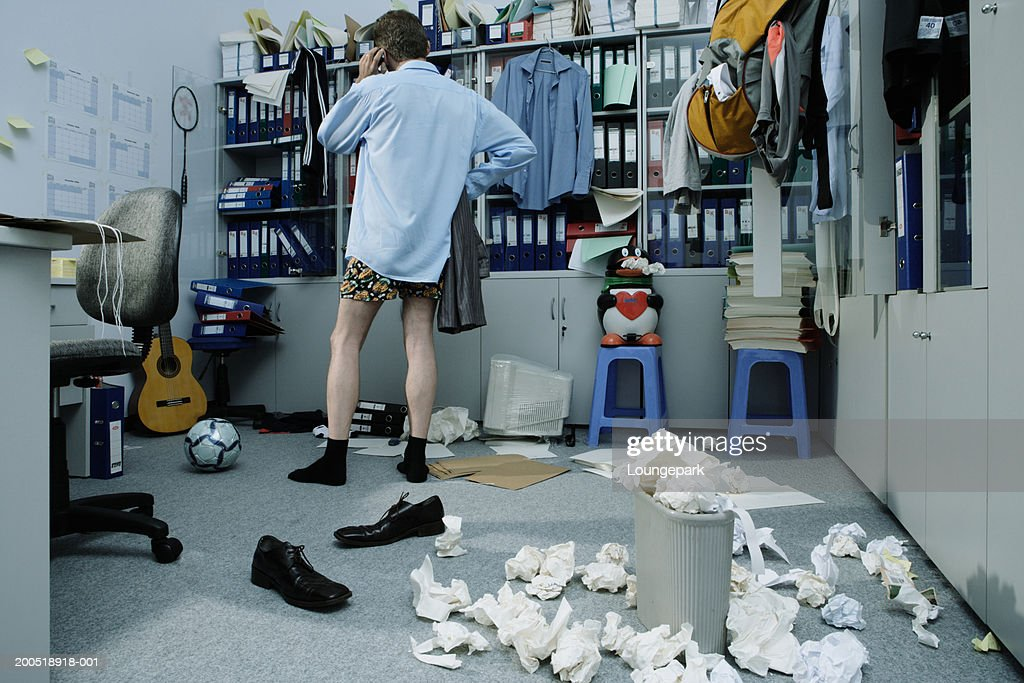 Half Dressed Businessman In Messy Office Using Phone Rear View