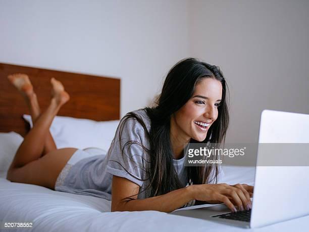 Die Hälfte gekleidete Frau Leg dich auf Bett Tippen auf einem Computer