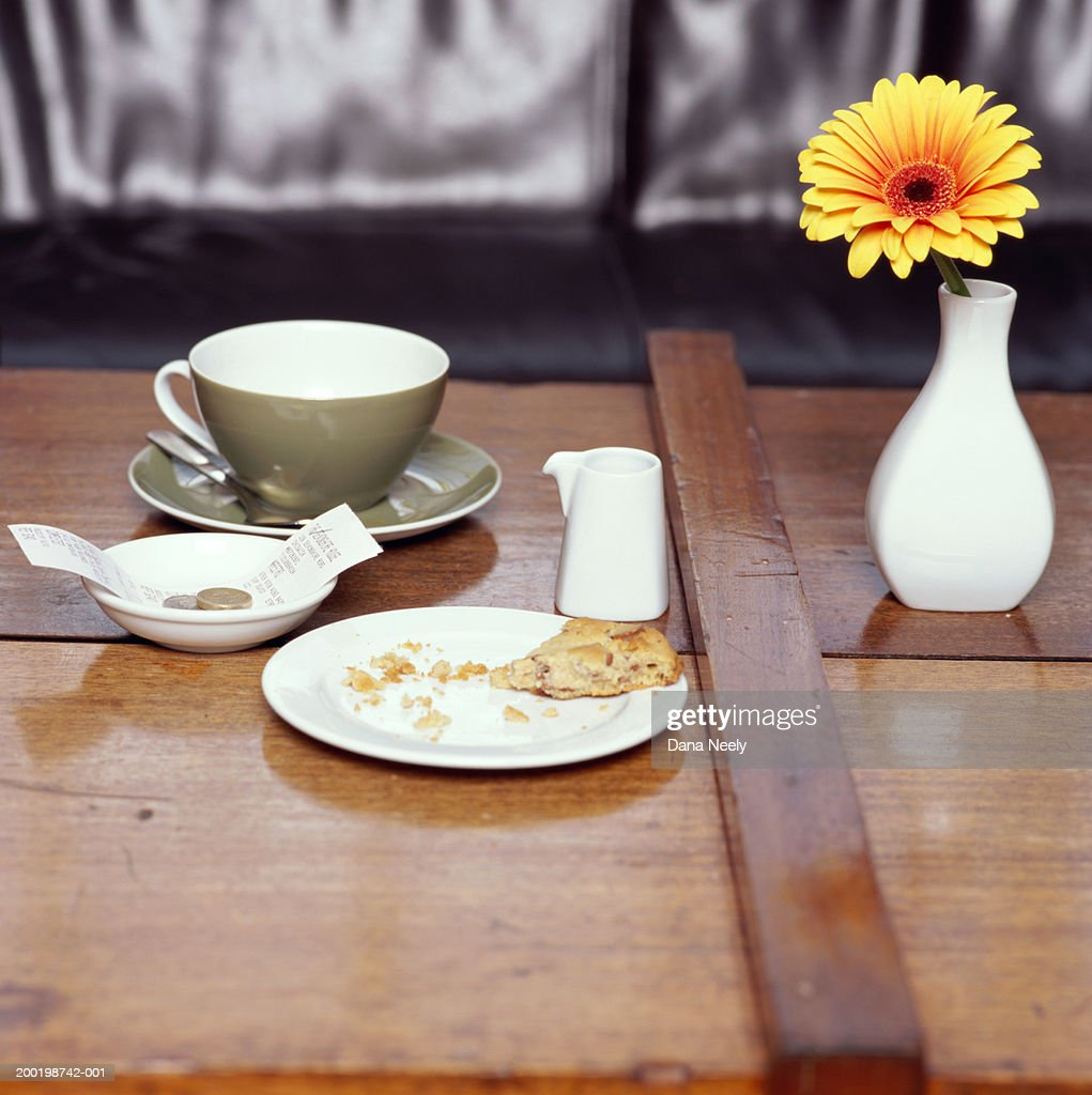 Half eaten biscuit, flower,  and coffee cup on table : ストックフォト