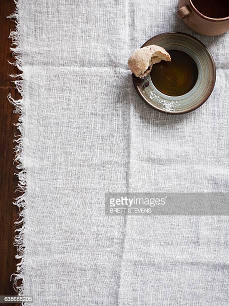 Half eaten bread roll on plate on muslin cloth