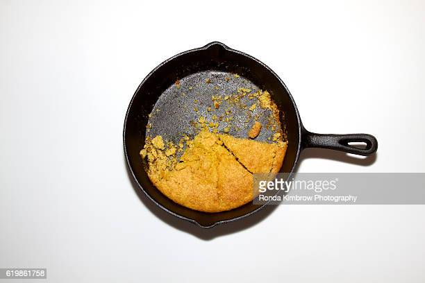 Half eaten cornbread in a cast iron skillet isolated on a white background