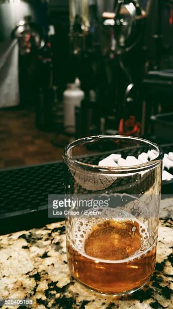 half empty glass of beer on table - rio rancho stock pictures, royalty-free photos & images