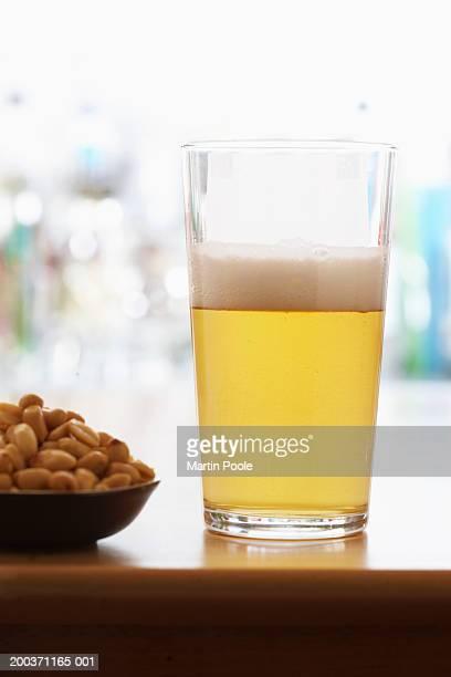Half filled pint of beer by peanuts