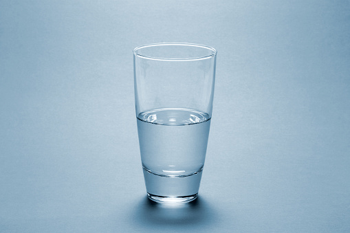 Half full water glass over blue background 92003014