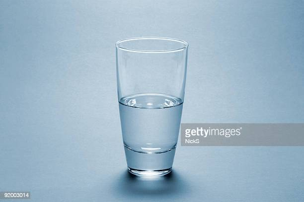 half full water glass over blue background - drinking glass stock pictures, royalty-free photos & images