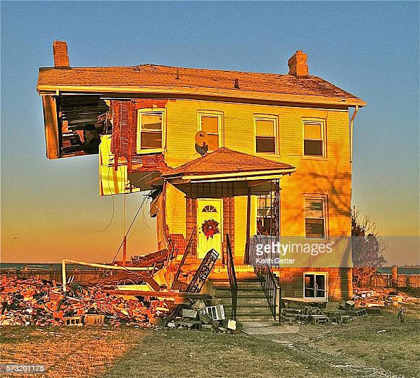 Six weeks after Super Storm Sandy hit Union Beach New Jersey half of a house still stands in the waning light of a clear day with a hopeful holiday...