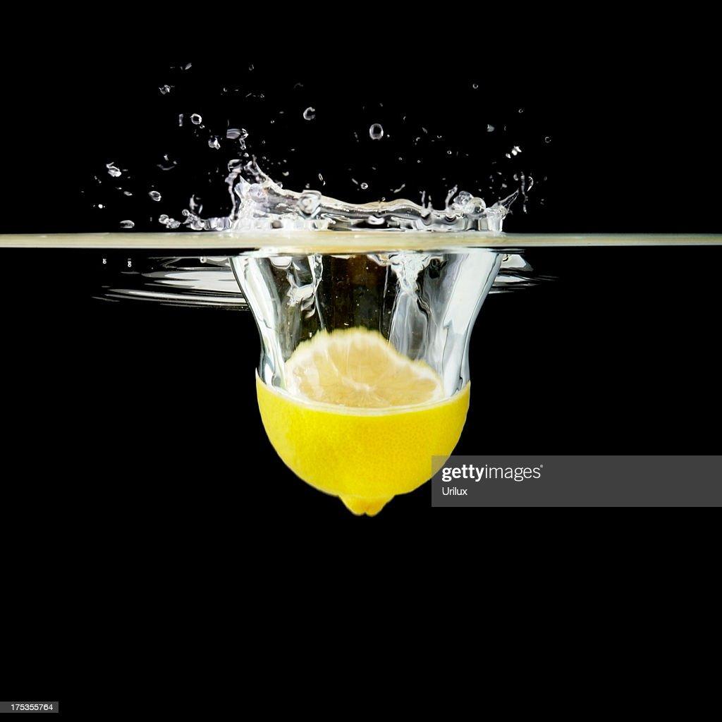 Half lemon falling into water : Stock Photo