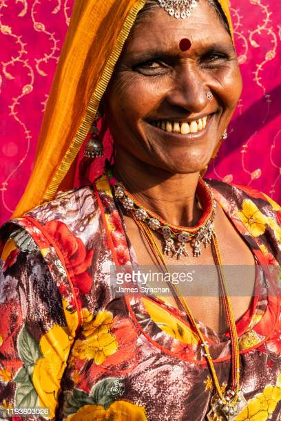 half length length portrait of mid-adult rajasthani woman with bright orange veil and yellow and red dress, in sunlight, against a pink background, pushkar fair, pushkar, rajasthan, india (model release) - james strachan stock pictures, royalty-free photos & images