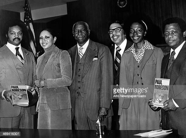 Half length portrait of a group of men and women holding copies of 'Paul Robeson, The Great Forerunner' by the editors of Freedomways, 1980.