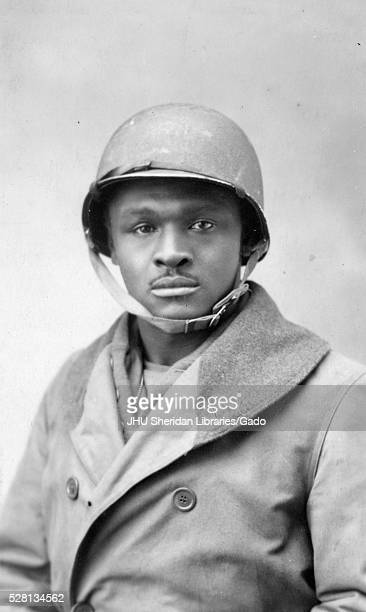 Half portrait of an African American World War I soldier wearing a doublebreasted jacket and helmet neutral facial expression 1920