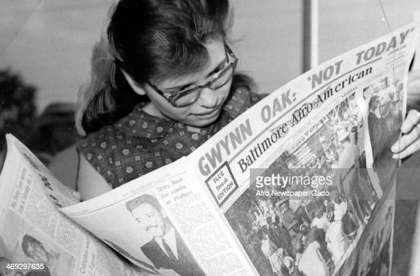 Half length portrait of Ann Knich from New York reading about the mass demonstrations at Gwynn Oak Park reading a copy of the Afro American newspaper...