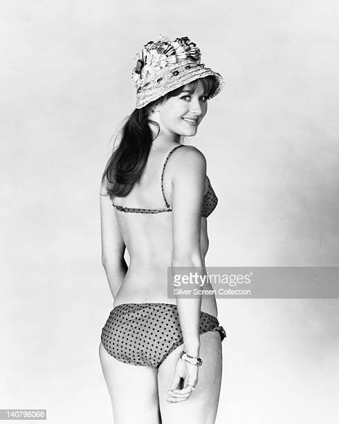 Half length portrait of Gabriella Licudi Moroccanborn British actress wearing a polka dot bikini and a beach hat in a studio portrait against a white...