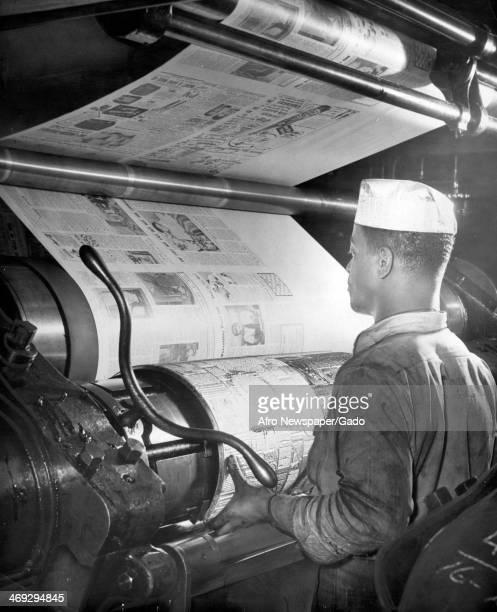 A half length portrait of pressman Joseph Goldman placing a metal plate on AFRO's Goss press in the print room Baltimore Maryland 1960