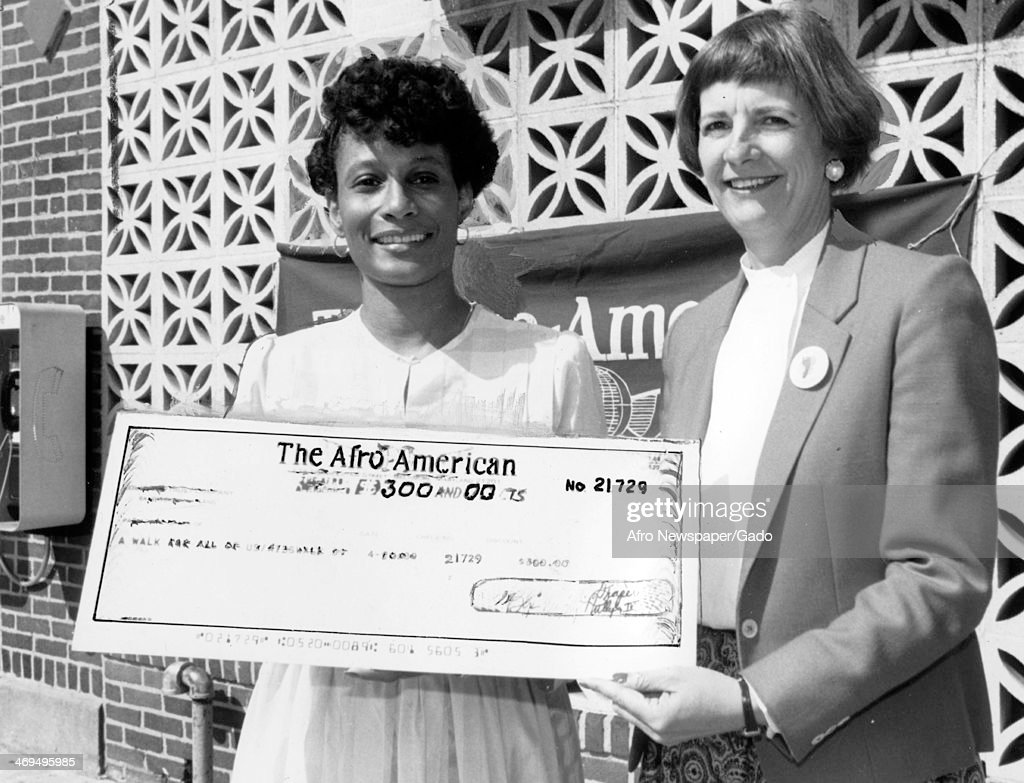 A half length portrait of Reverend Frances Murphy Draper, great granddaughter of the founder of the Afro American, holding a check together with Sandra [?], 1980.