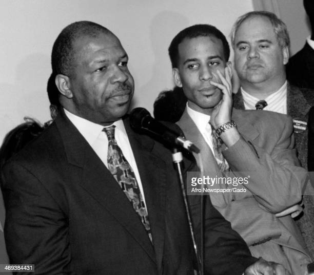 A half length portrait of US Representative Elijah Cummings standing at a microphone with two men standing beside him Maryland 2000