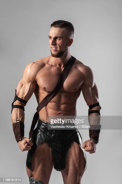 half length portrait of young handsome muscular man gladiator - gladiator stock pictures, royalty-free photos & images