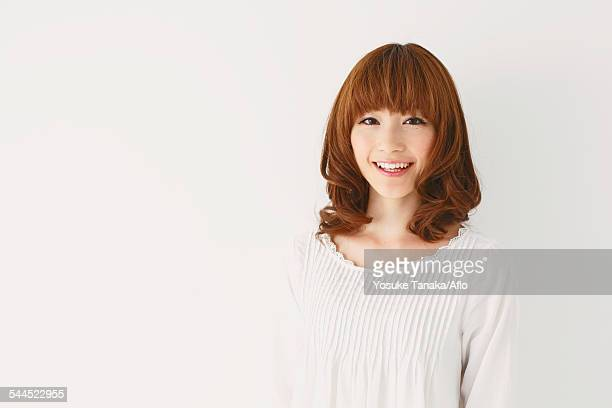Half length portrait of young Japanese woman against white background