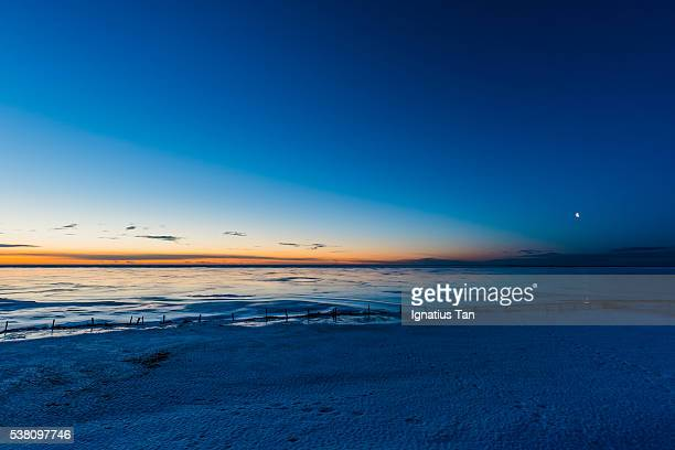 half moon setting at sunrise with reflection over a frozen lagoon - ignatius tan stock photos and pictures