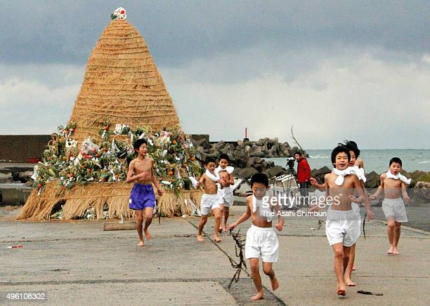 Half naked boys holding a seaweed runs after rounding three times around the 4meter ornament made of straw called 'Tondo' to purify the houses of the...