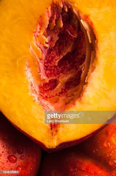 Half of a juicy peach resting on two uncut peaches, full frame