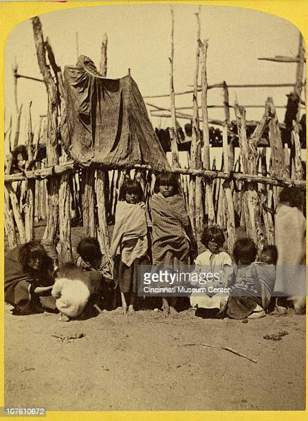 Half of a stereoscope portrait of Pueblo Tesuque Indian children standing in front of a fence Santa Fe New Mexico ca 1880s