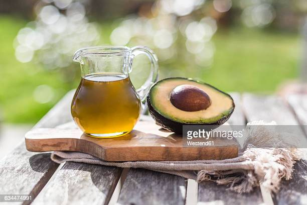 Half of avocado and glass jug of avocado oil on wooden board
