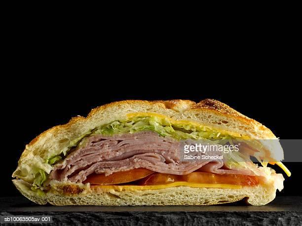 Half of deli sandwich on black slate, close-up