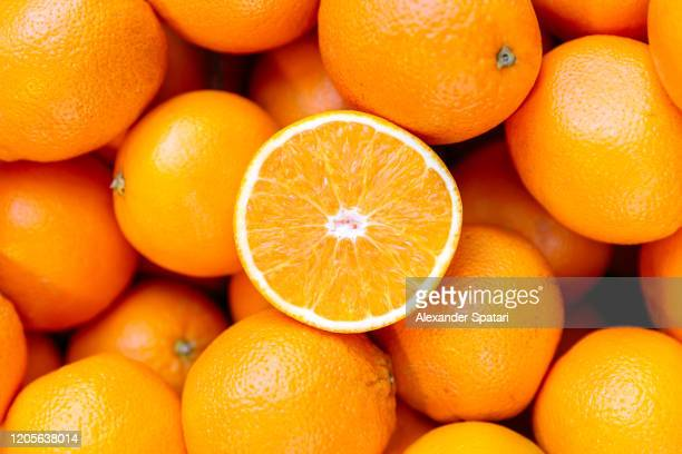 half of orange on the heap of oranges - arancione foto e immagini stock