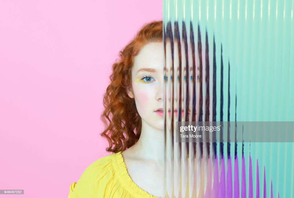 half of woman's face obscured by glass : Stock Photo