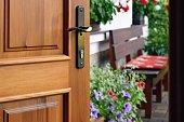 Half opened door into the beautiful summer terrace and  blooming garden