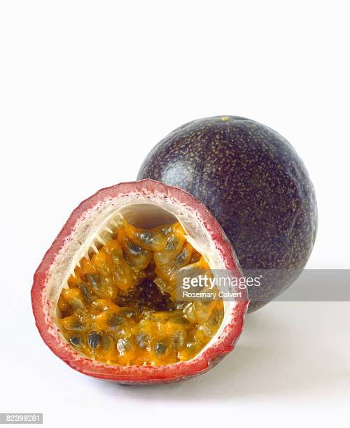 Half passion fruit in front of whole passion fruit