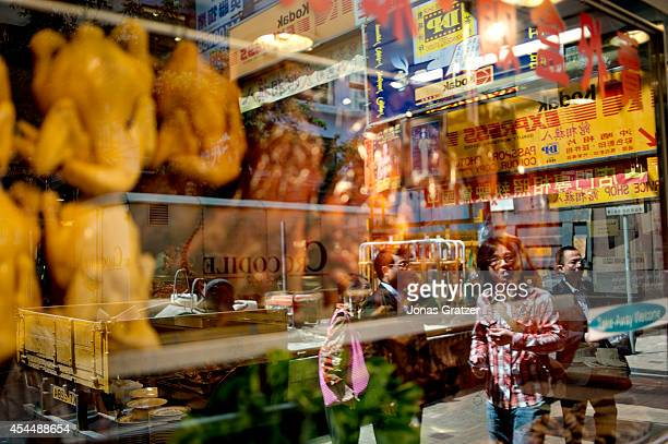 A half reflected image on the glass of a food stall that sells duck noodles