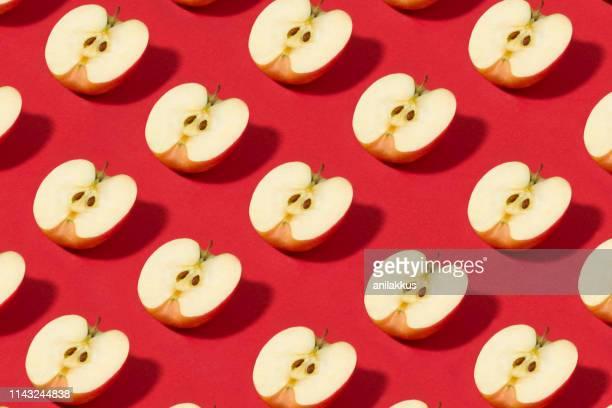 half sliced apples pattern on red background - mela foto e immagini stock