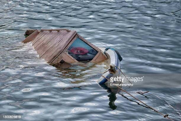half sunken wooden fishing boat,inciaralti marina. - emreturanphoto stock pictures, royalty-free photos & images