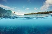 half underwater shot of surfer surfing a wave in Indo