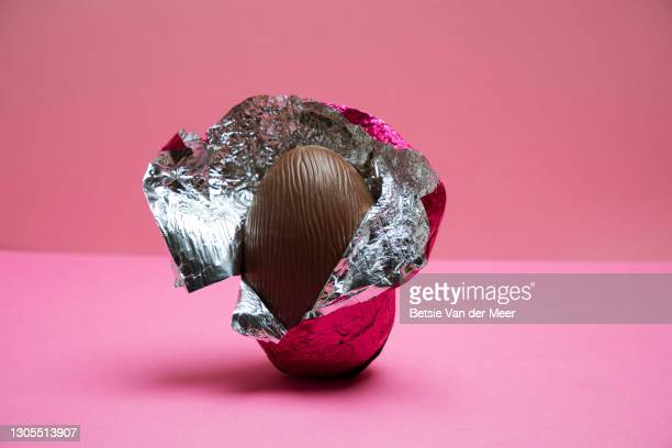 a half unwrapped easter egg on a pink background. - easter egg stock pictures, royalty-free photos & images