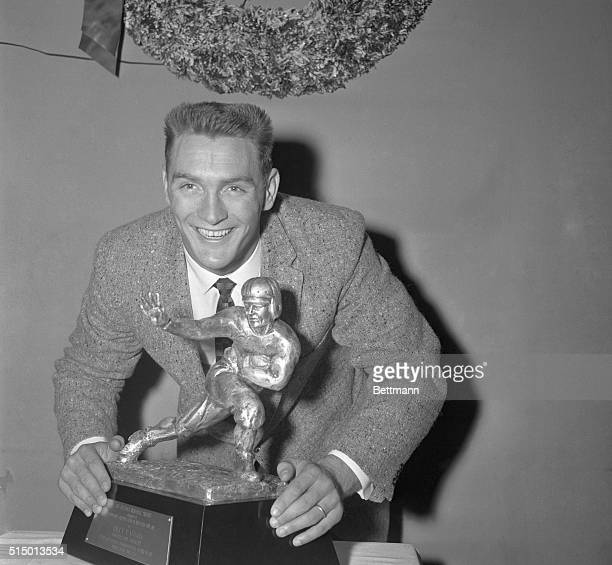 Halfback Billy Cannon of Louisiana State University, standing under a Christmas wreath, gleefully holds the 1959 Heisman Memorial Trophy, which he...