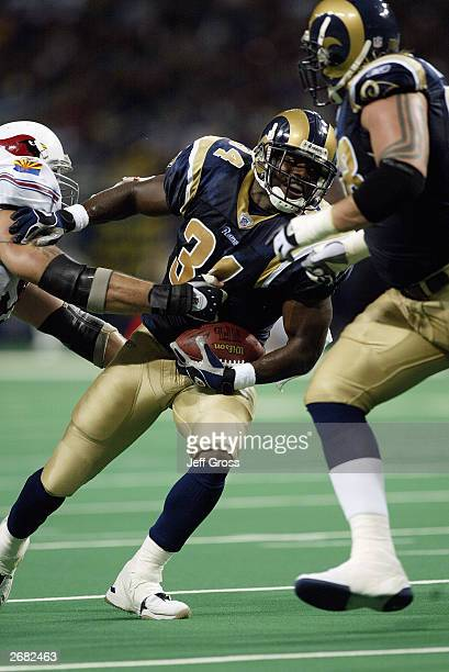 Halfback Lamar Gordon of the St Louis Rams looks to break free from an Arizona Cardinal tackler on September 28 2003 at the Edward Jones Dome in St...