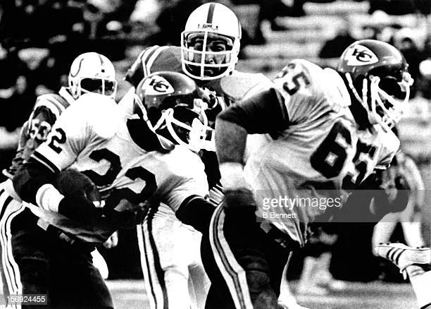 Halfback Ted McKnight of the Kansas City Chiefs follows his guard Tom Condon as they run past Joe Ehrmann of the Baltimore Colts on December 9 1979...