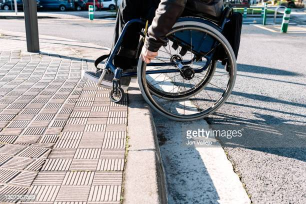 half-body details of a man sitting in his wheelchair climbing up a curb that is not wheelchair accessible. - capital region stock pictures, royalty-free photos & images